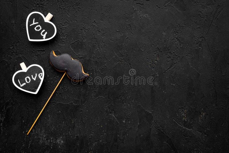 Concepto del cumpleaños del ` s de los hombres Galletas en la forma del bigote Los corazones con las letras le aman en copia negr imagenes de archivo