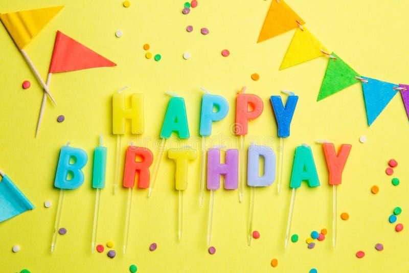 Concepto del cumpleaños - velas con las letras 'feliz cumpleaños 'y confeti fotos de archivo libres de regalías