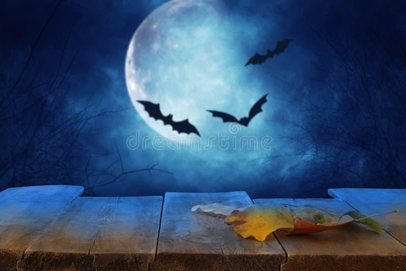 Concepto del día de fiesta de Halloween Vacie la tabla rústica delante del cielo nocturno asustadizo y brumoso con los palos negr imagen de archivo