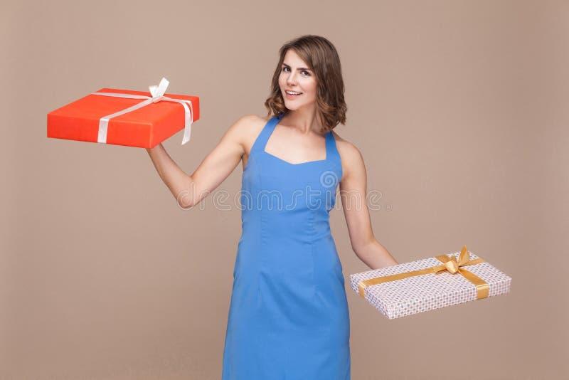 Concepto del día de fiesta o del cumpleaños Mujer de la felicidad que sostiene dos regalos b fotos de archivo libres de regalías