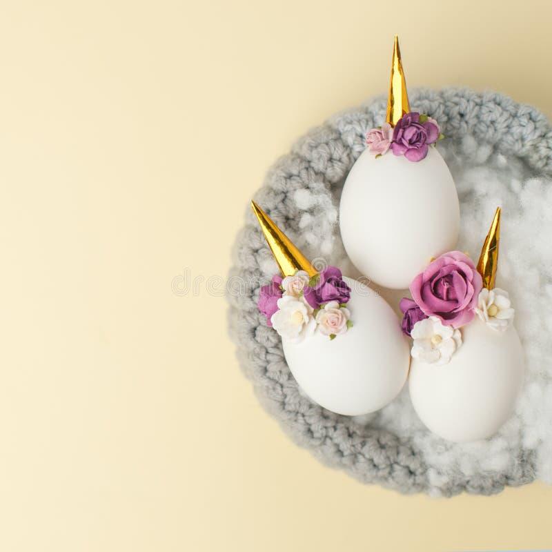 Concepto del día de fiesta de Pascua con los huevos hechos a mano lindos, unicornio y la decoración de la flor en jerarquía del p imagen de archivo libre de regalías