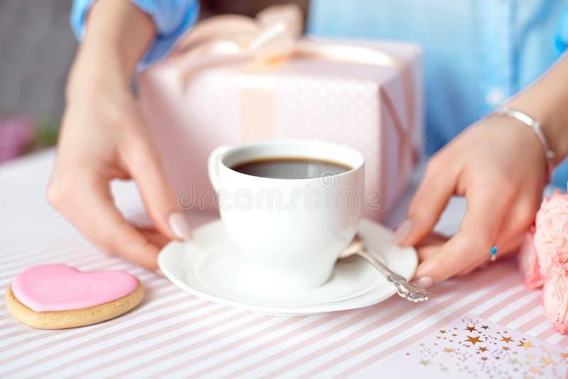 Concepto del día de madre - un regalo para las manos de las mujeres con una taza blanca de café y de rosas Copie el espacio imagenes de archivo