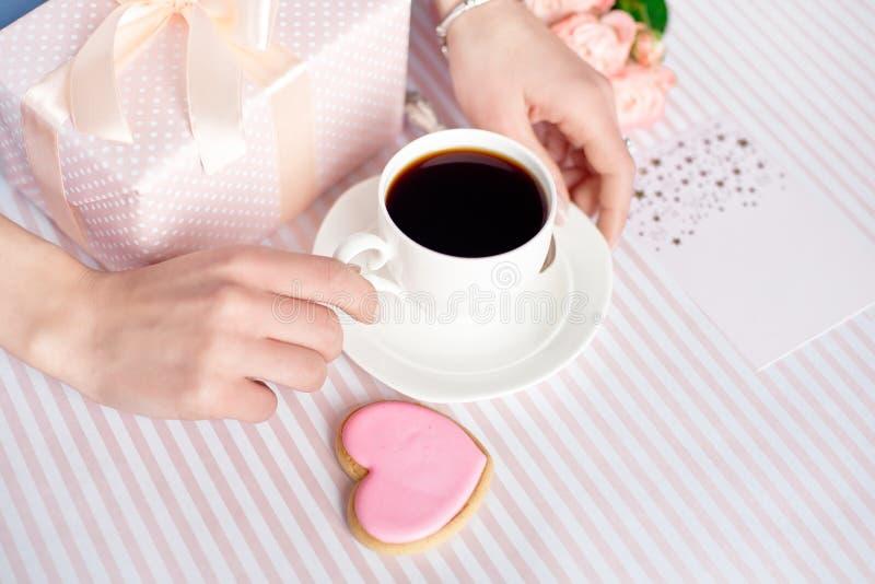 Concepto del día de madre - un regalo para las manos de las mujeres con una taza blanca de café y de rosas Copie el espacio imagen de archivo libre de regalías