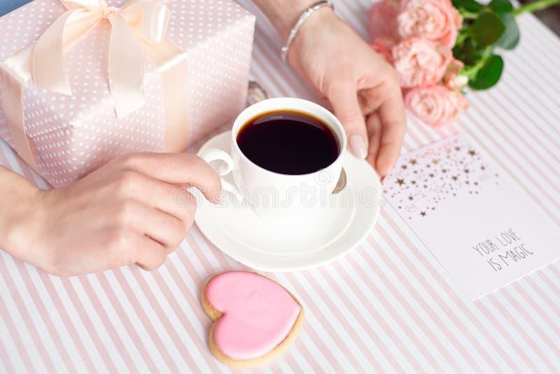 Concepto del día de madre - un regalo para las manos de las mujeres con una taza blanca de café y de rosas Copie el espacio fotografía de archivo