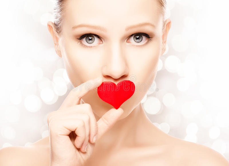 Concepto del día de tarjeta del día de San Valentín. muchacha con un corazón rojo en los labios fotografía de archivo libre de regalías