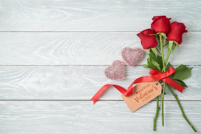 Concepto del día de tarjeta del día de San Valentín con las flores, la etiqueta del regalo y formas color de rosa del corazón del foto de archivo