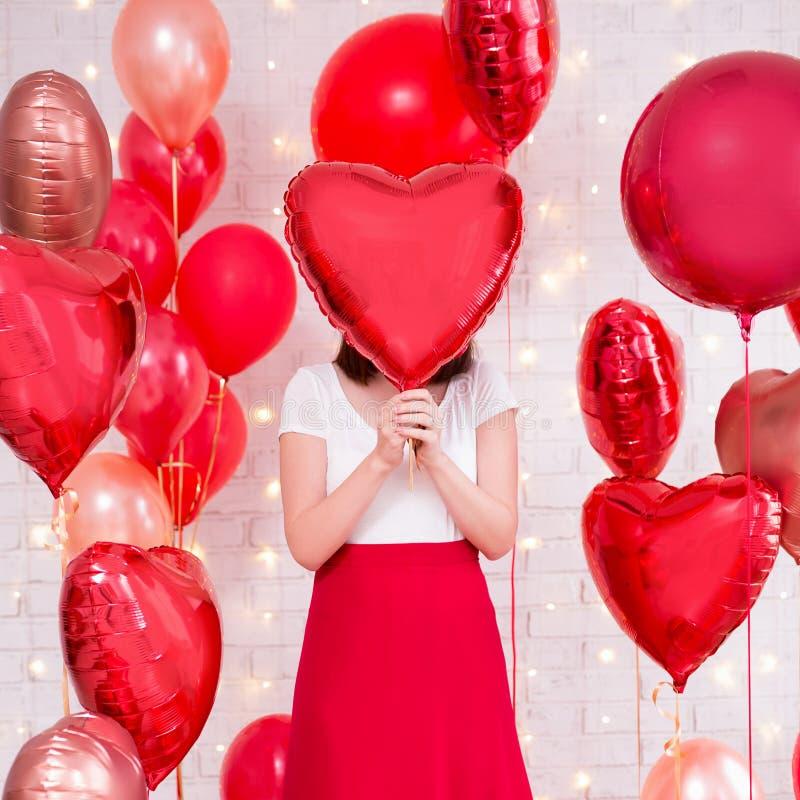 Concepto del día de tarjeta del día de San Valentín - mujer que cubre su cara con el globo en forma de corazón imágenes de archivo libres de regalías