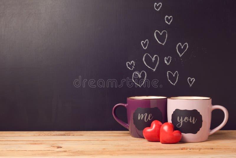Concepto del día del ` s de la tarjeta del día de San Valentín con los corazones y las tazas sobre fondo de la pizarra fotografía de archivo