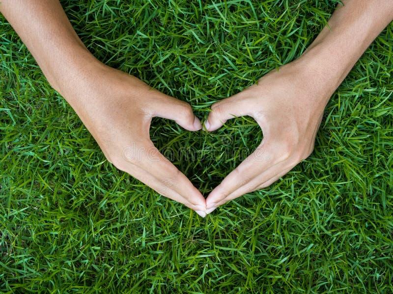 Concepto del día del ` s del amor y de la tarjeta del día de San Valentín mano masculina en la forma del corazón encendido foto de archivo libre de regalías