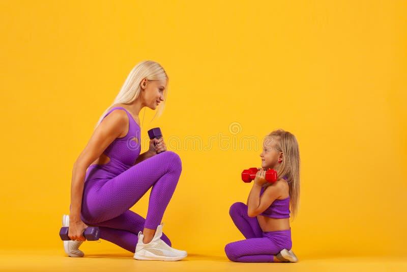 Concepto del día del ` s de la madre Ejercicio joven de la madre y de la hija así como pesas de gimnasia Mirada de la familia fotos de archivo