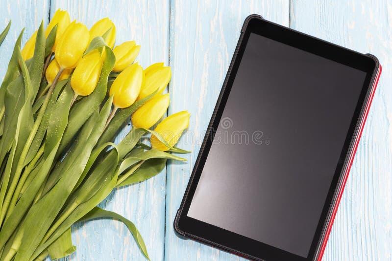 Concepto del día del ` s de la madre los tulipanes florecen en fondo de madera azul en colores pastel, al lado de la tableta con  imagenes de archivo