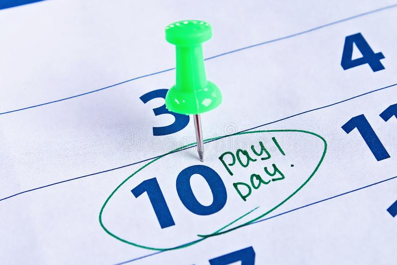 Concepto del d?a de paga Negocio, finanzas, dinero de los ahorros Calendario con el círculo de marcador en día de paga de la pala fotografía de archivo libre de regalías