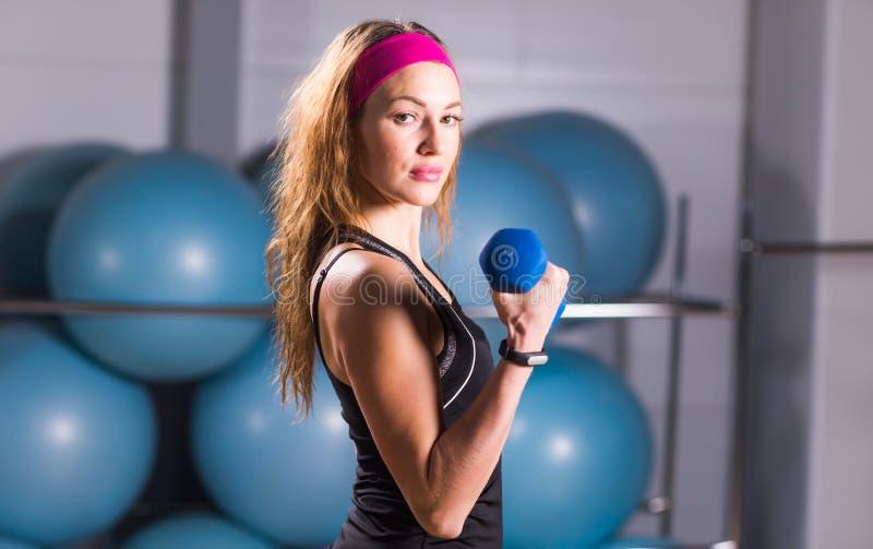 Concepto del deporte, de la aptitud, del entrenamiento y de la felicidad - manos deportivas de la mujer con pesas de gimnasia azu foto de archivo libre de regalías