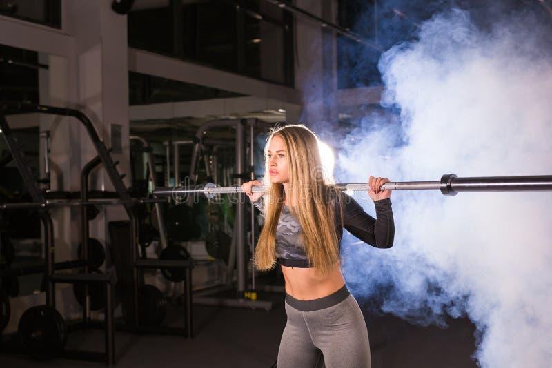 Concepto del deporte, de la aptitud, del entrenamiento y de la felicidad - mujer deportiva con el barbell en gimnasio fotografía de archivo