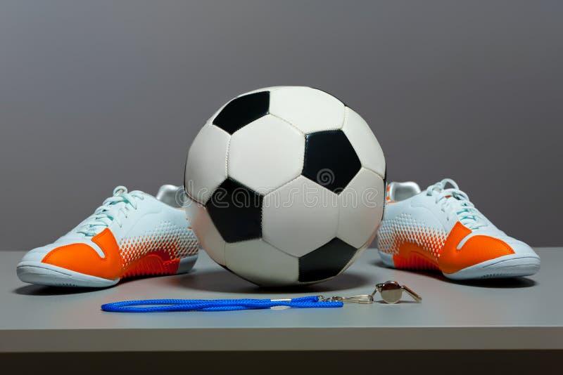 Concepto del deporte - zapatos, balón de fútbol y silbido. fotografía de archivo libre de regalías