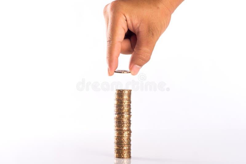 Concepto del dinero del ahorro preestablecido por la mano masculina que pone el stac de la moneda del dinero fotografía de archivo