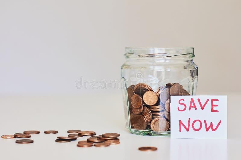 Concepto del dinero del ahorro Tarro de cristal por completo de monedas y de la reserva de la muestra ahora fotografía de archivo