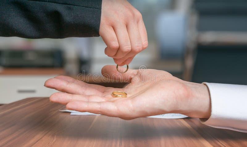 Concepto del divorcio El par joven se está divorciando La esposa vuelve el anillo a su marido imagen de archivo libre de regalías