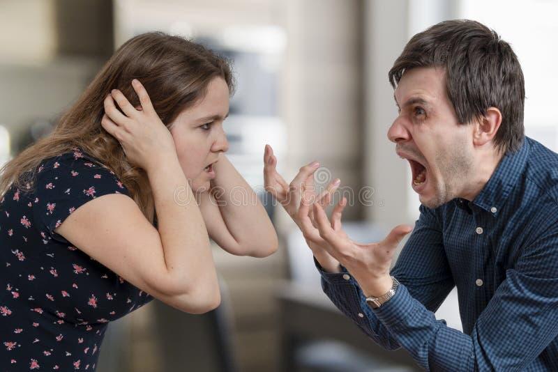 Concepto del divorcio Pares enojados jovenes que discuten y que gritan imagen de archivo
