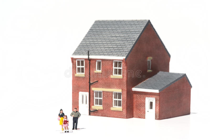 Concepto del domicilio familiar con la casa y la gente modelo en el backgro blanco imagen de archivo libre de regalías