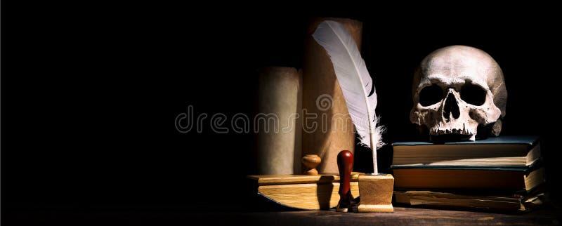 Concepto del drama o del teatro y de la literatura Inkstand viejo con la pluma cerca de volutas con el cr?neo en los libros contr fotografía de archivo libre de regalías