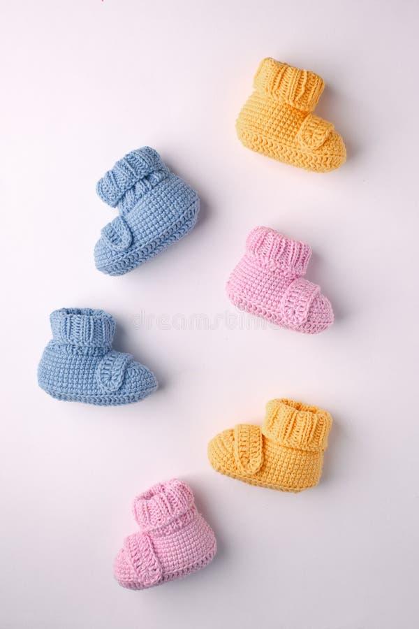 Concepto del embarazo, tres pares de botines del bebé en un fondo ligero, endecha plana, modelo fotografía de archivo