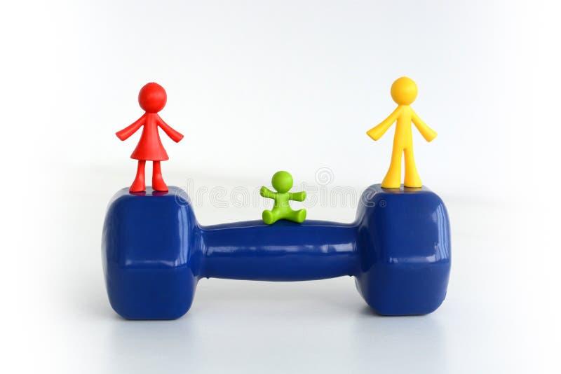 Concepto del equipo de la familia con la miniatura humana en pesa de gimnasia foto de archivo