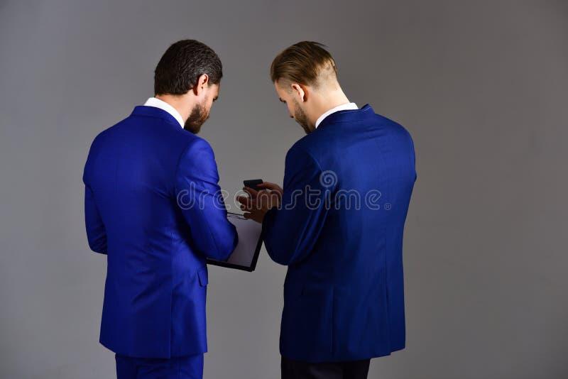 Concepto del escape de la información Los hombres de negocios miran el documento secreto foto de archivo