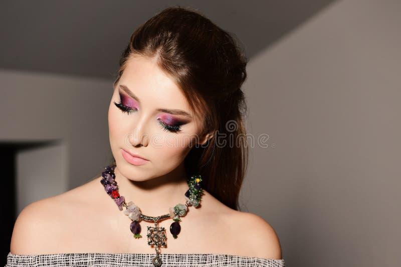 Concepto del estilo y de la moda: modelo con el collar colorido que mira abajo imagenes de archivo