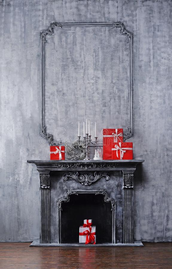 Concepto del fondo de la Navidad Chimenea antigua con una palmatoria y las cajas de regalo fotografía de archivo
