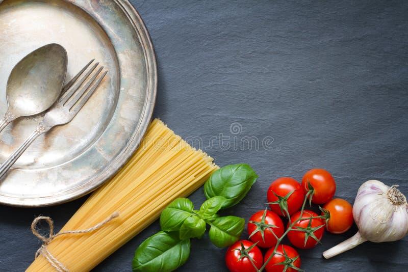 Concepto del fondo del extracto de la comida del ajo del tomate de la albahaca de las pastas en el mármol negro imágenes de archivo libres de regalías