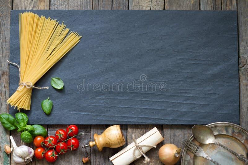 Concepto del fondo del extracto de la comida del ajo del tomate de la albahaca de las pastas en el mármol negro fotos de archivo