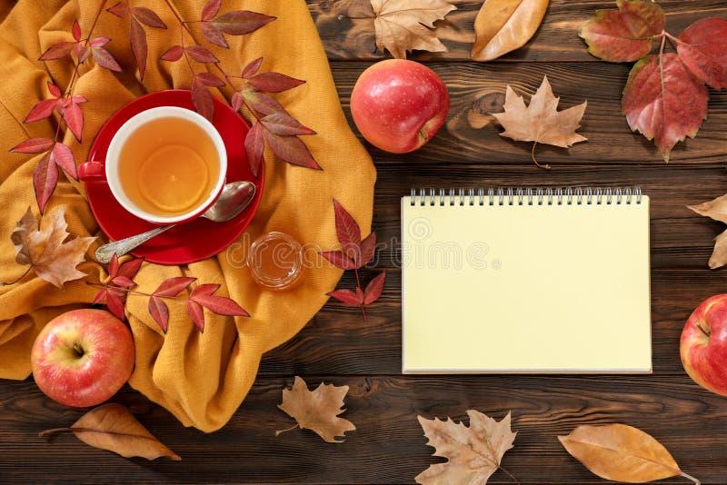 Concepto del fondo del otoño - taza roja de té con el pedazo de limón, de hojas secadas, de manzanas rojas, de miel y de cuaderno foto de archivo