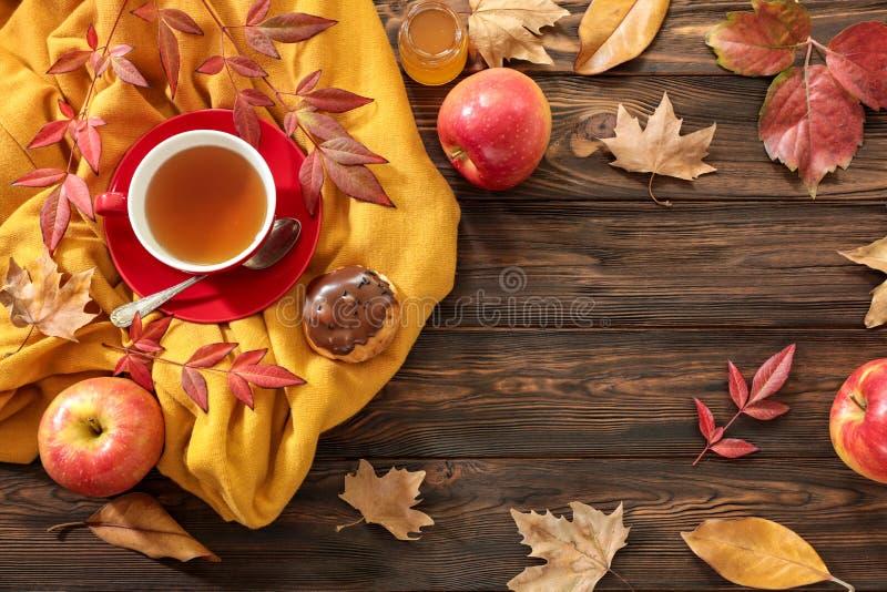 Concepto del fondo del otoño - taza roja de té negro, hojas secadas, manzanas rojas, buñuelo del chocolate en un fondo de madera  imágenes de archivo libres de regalías