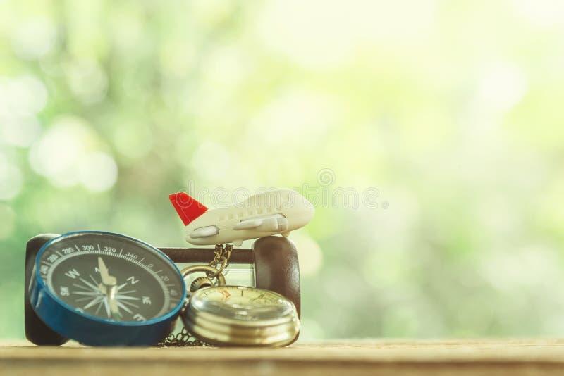 Concepto del fondo del viaje Pequeño aeroplano con el reloj de oro y el co imagen de archivo