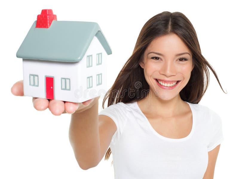 Concepto del hogar/de la casa - mujer que sostiene la mini casa imagen de archivo