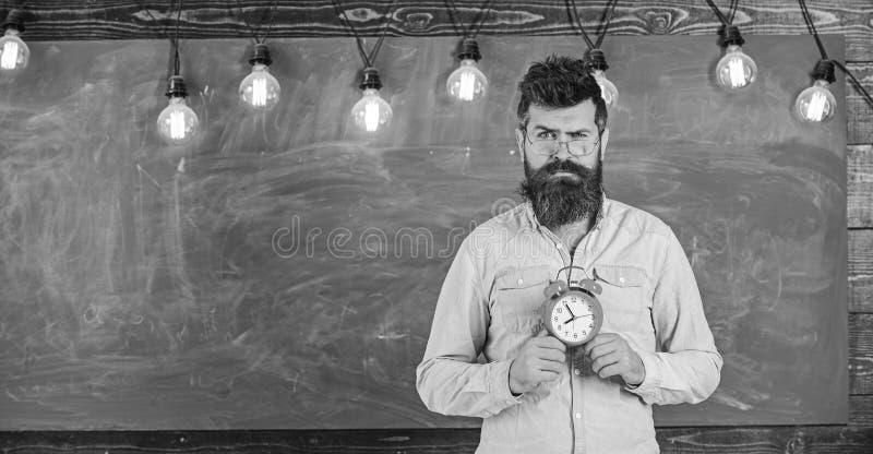 Concepto del horario de la escuela El hombre con la barba y el bigote en cara sospechosa se colocan en sala de clase El inconform foto de archivo