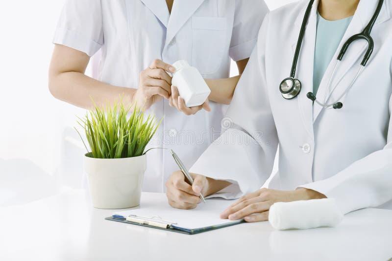 Concepto del hospital y de la medicina, doctor y enfermera o farmacéutico discutiendo sobre la droga paciente foto de archivo