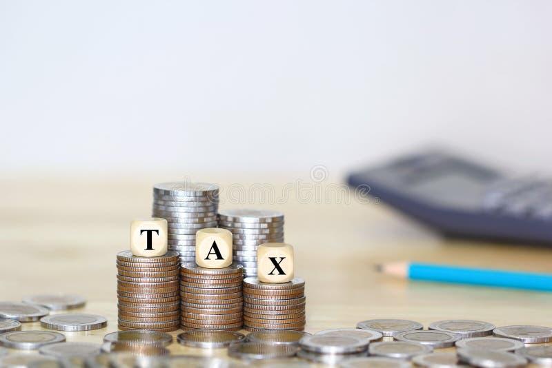 Concepto del impuesto, bloque de madera en el amontonamiento del dinero de las monedas en el fondo blanco foto de archivo libre de regalías