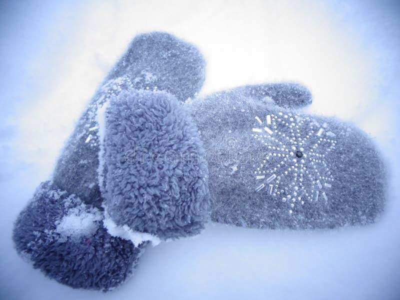 Concepto del invierno con las manoplas grises en la nieve foto de archivo libre de regalías