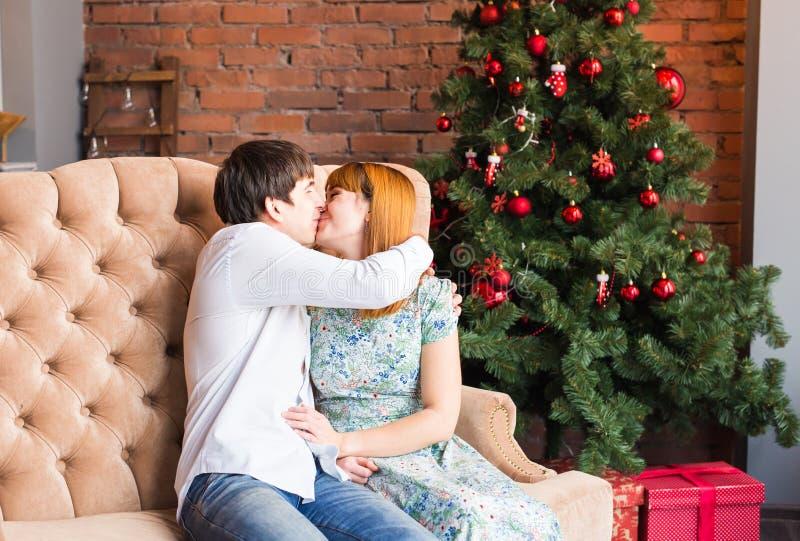 Concepto del invierno, del amor, de los pares, de la Navidad y de la gente - hombre y mujer que se besan sobre fondo del árbol de foto de archivo