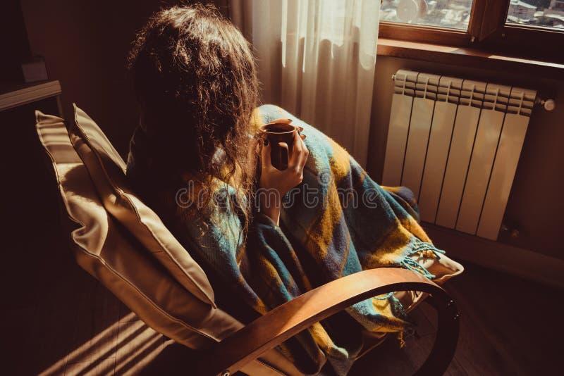 Concepto del invierno Mujer joven que se sienta en silla moderna cómoda cerca del radiador con la taza de té envuelta en manta ca fotos de archivo