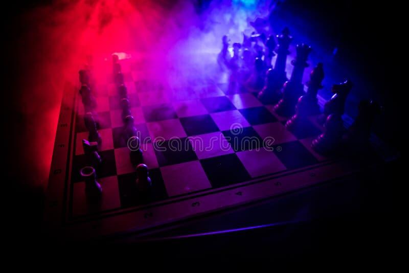 Concepto del juego de mesa del ajedrez de ideas y de competencia del negocio El ajedrez figura en un fondo oscuro con humo y nieb fotos de archivo