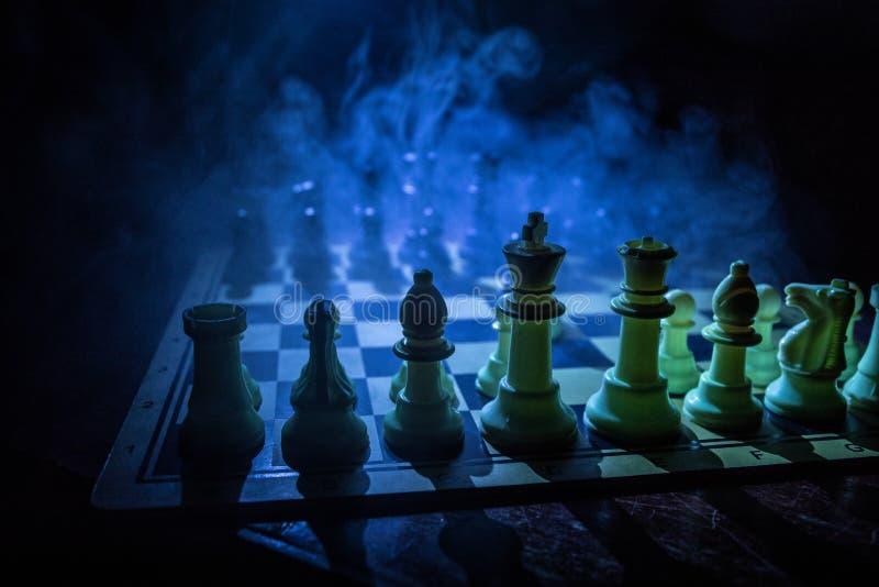 Concepto del juego de mesa del ajedrez de ideas y de competencia del negocio El ajedrez figura en un fondo oscuro con humo y nieb fotografía de archivo