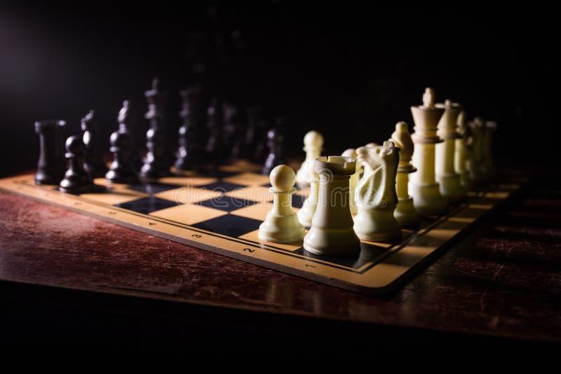 Concepto del juego de mesa del ajedrez de ideas y de competencia del negocio El ajedrez figura en un fondo oscuro con humo y nieb imágenes de archivo libres de regalías