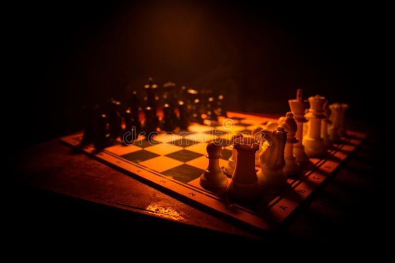 Concepto del juego de mesa del ajedrez de ideas y de competencia del negocio El ajedrez figura en un fondo oscuro con humo y nieb foto de archivo