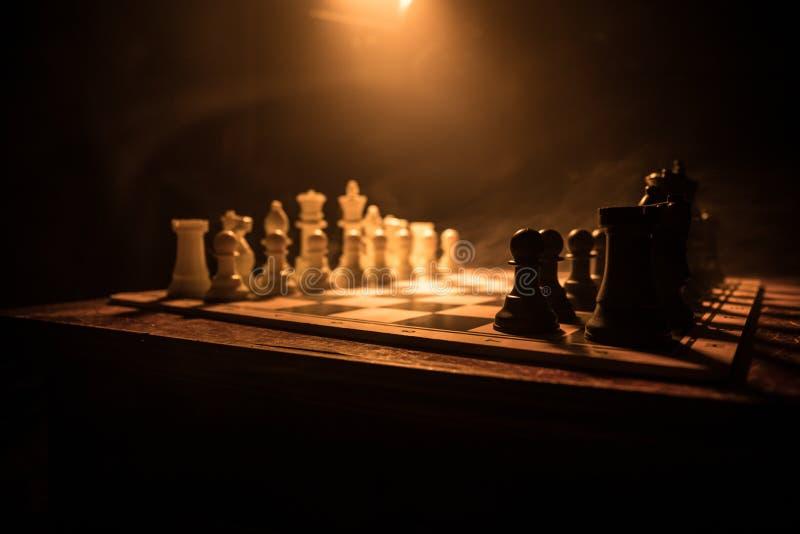 Concepto del juego de mesa del ajedrez de ideas y de competencia del negocio El ajedrez figura en un fondo oscuro con humo y nieb fotografía de archivo libre de regalías