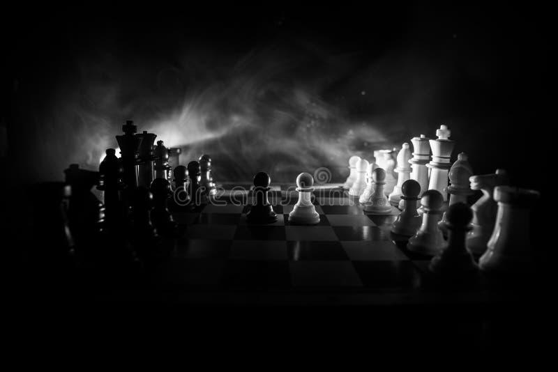 Concepto del juego de mesa del ajedrez de ideas y de competencia del negocio El ajedrez figura en un fondo oscuro con humo y nieb imagen de archivo