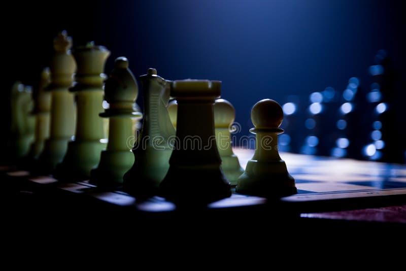 Concepto del juego de mesa del ajedrez de ideas y de competencia del negocio El ajedrez figura en un fondo oscuro con humo y nieb imagenes de archivo