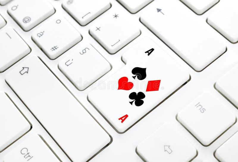 Concepto del juego online del póker o del casino. Llave en el teclado blanco fotografía de archivo